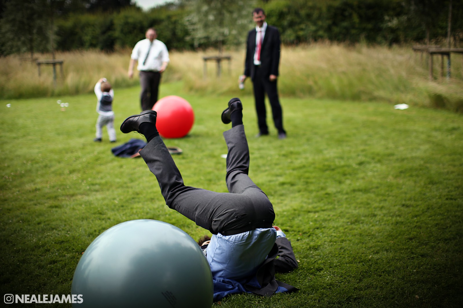 A colour photo of a wedding guest falling off a space ball bouncer