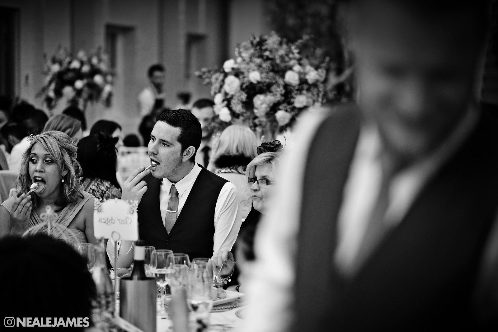 Monochrome image of guests mimicking each other as they eat