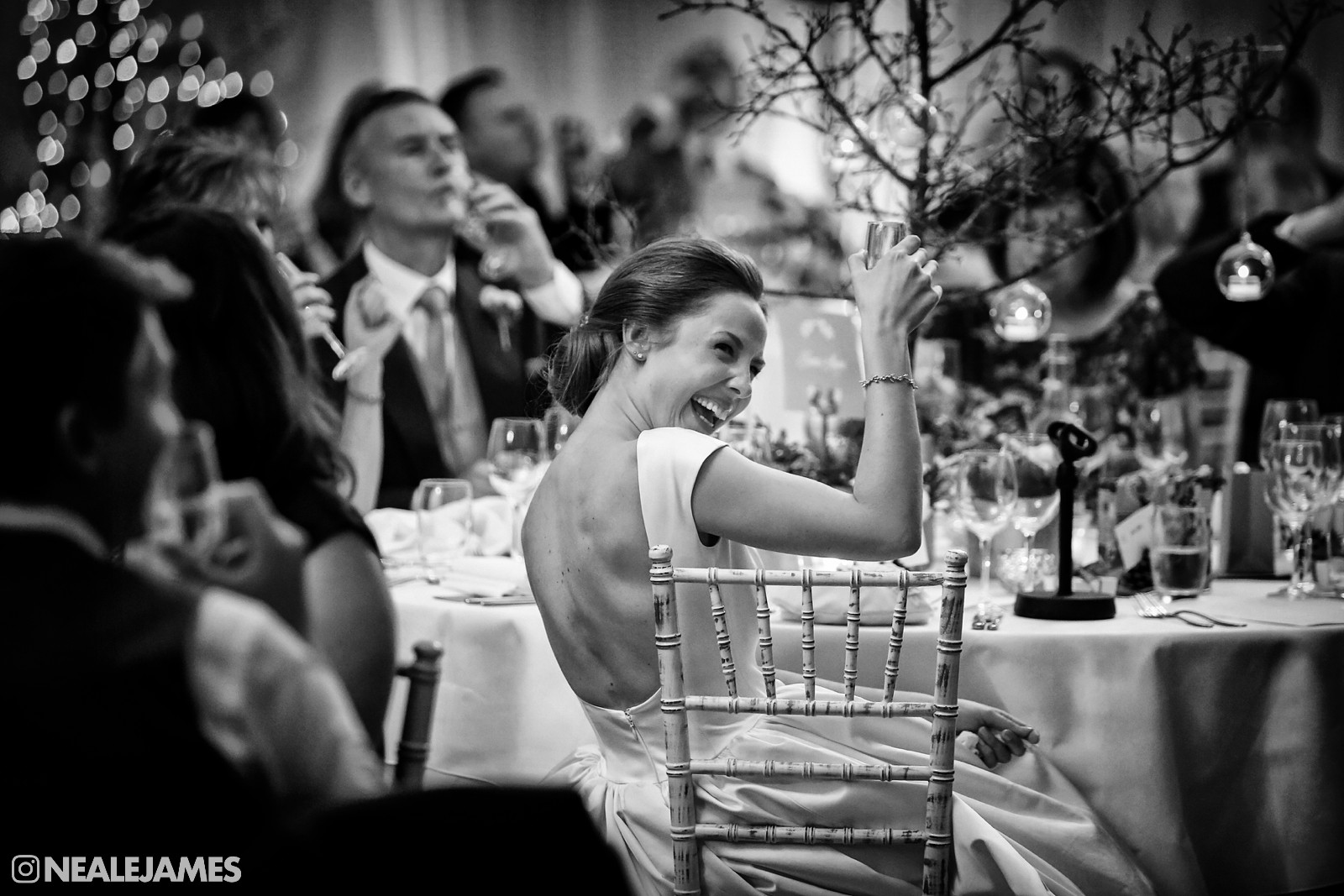 Black and white image of a bride raising a toast during the speeches