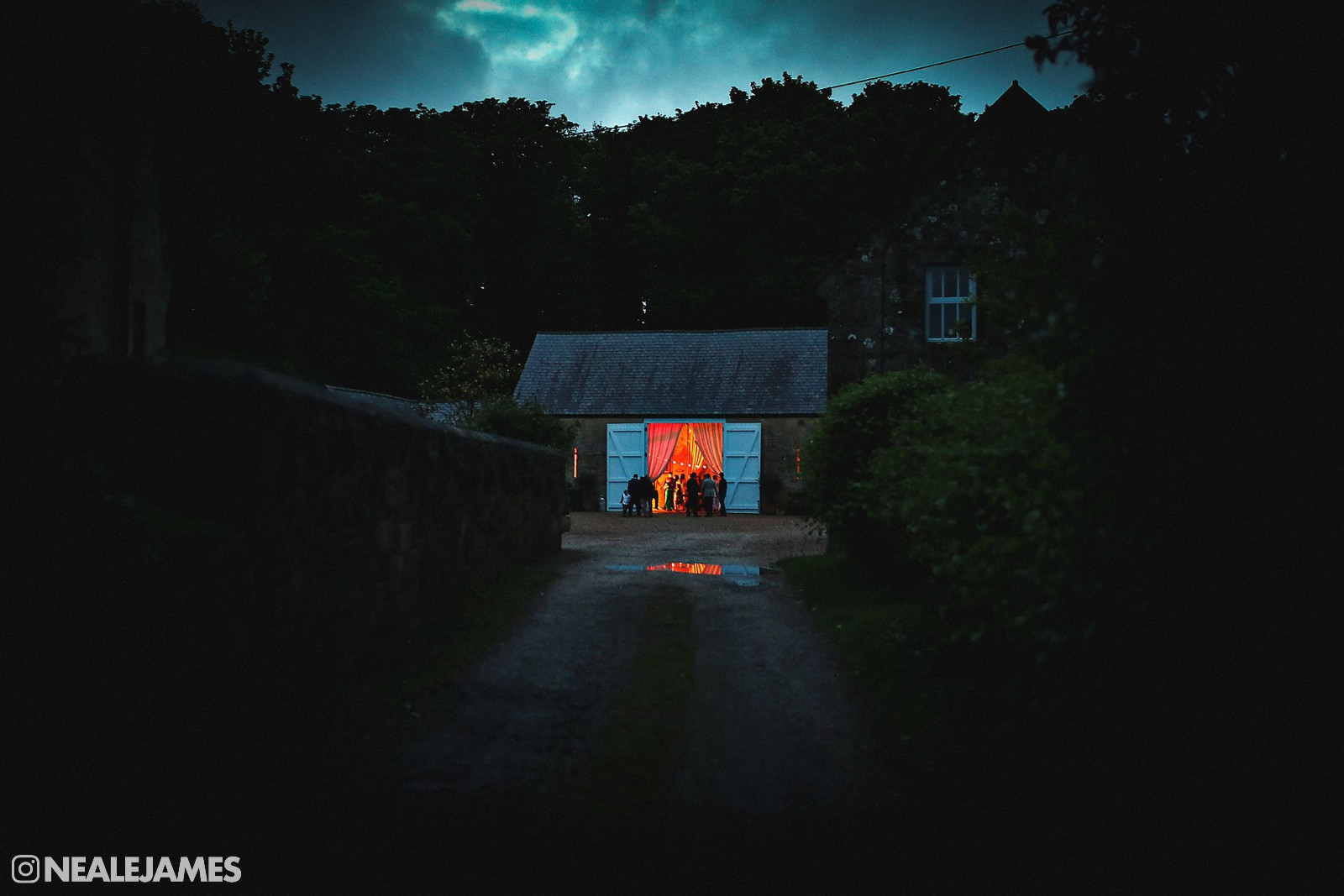 Colour picture to go on the Wedding Photography Gallery page. Late night picture where you see into a barn illuminated only by the band's lights.
