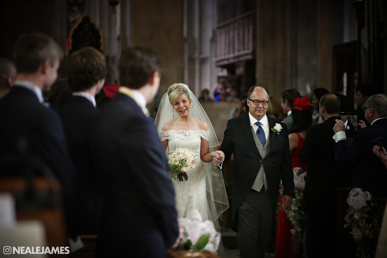 Colour picture of a bride being lead into a wedding chapel ceremony by her father