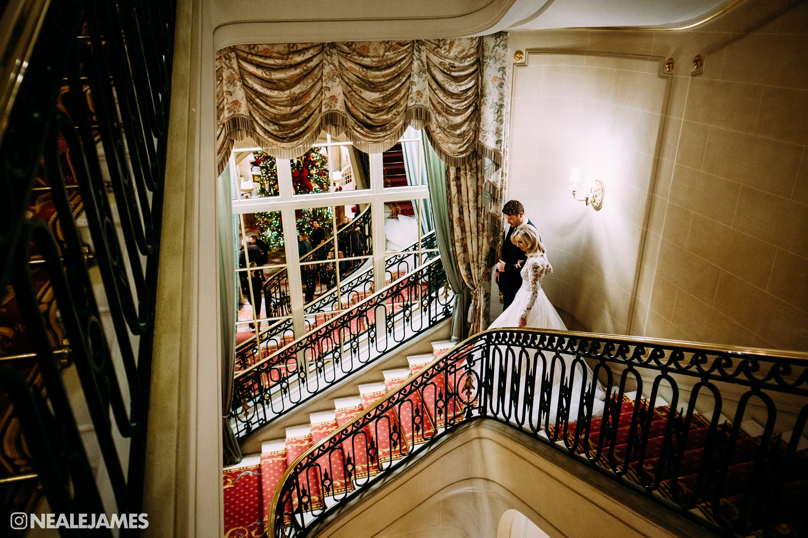 Colour photo of a bride being walked to her wedding by her brother at The Ritz in London