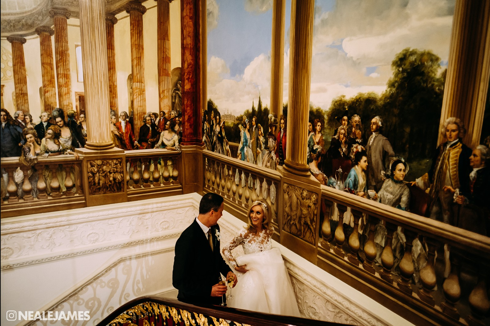 A colour photo of Ricki and bride Charlotte on the stairs at The Ritz in London