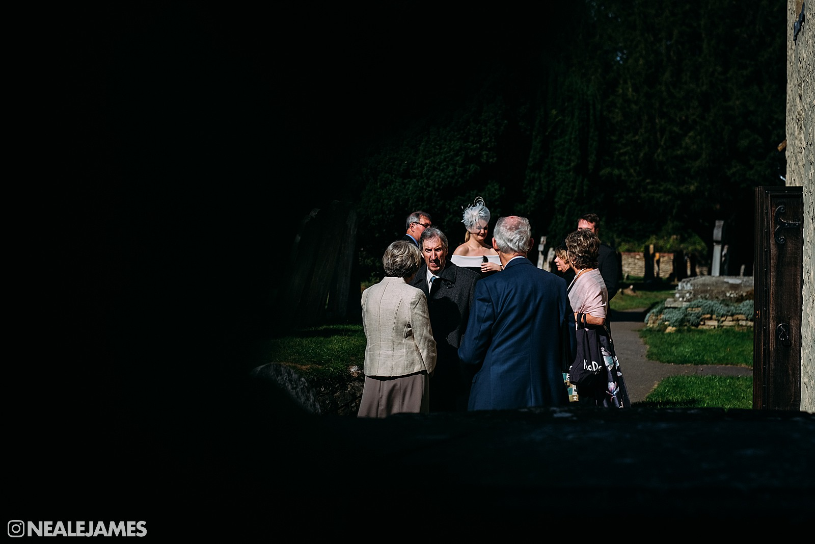 Colour picture of wedding guests outside a church in Surrey, England