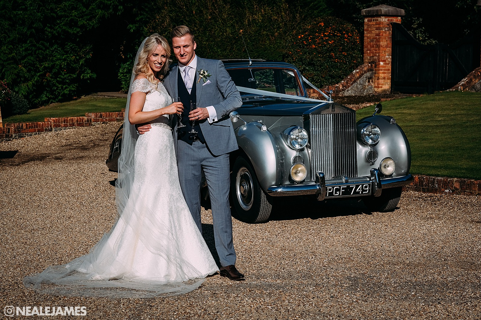 Colour picture of a bride and groom after they have just arrived at the Bijou wedding venue, Cain Manor
