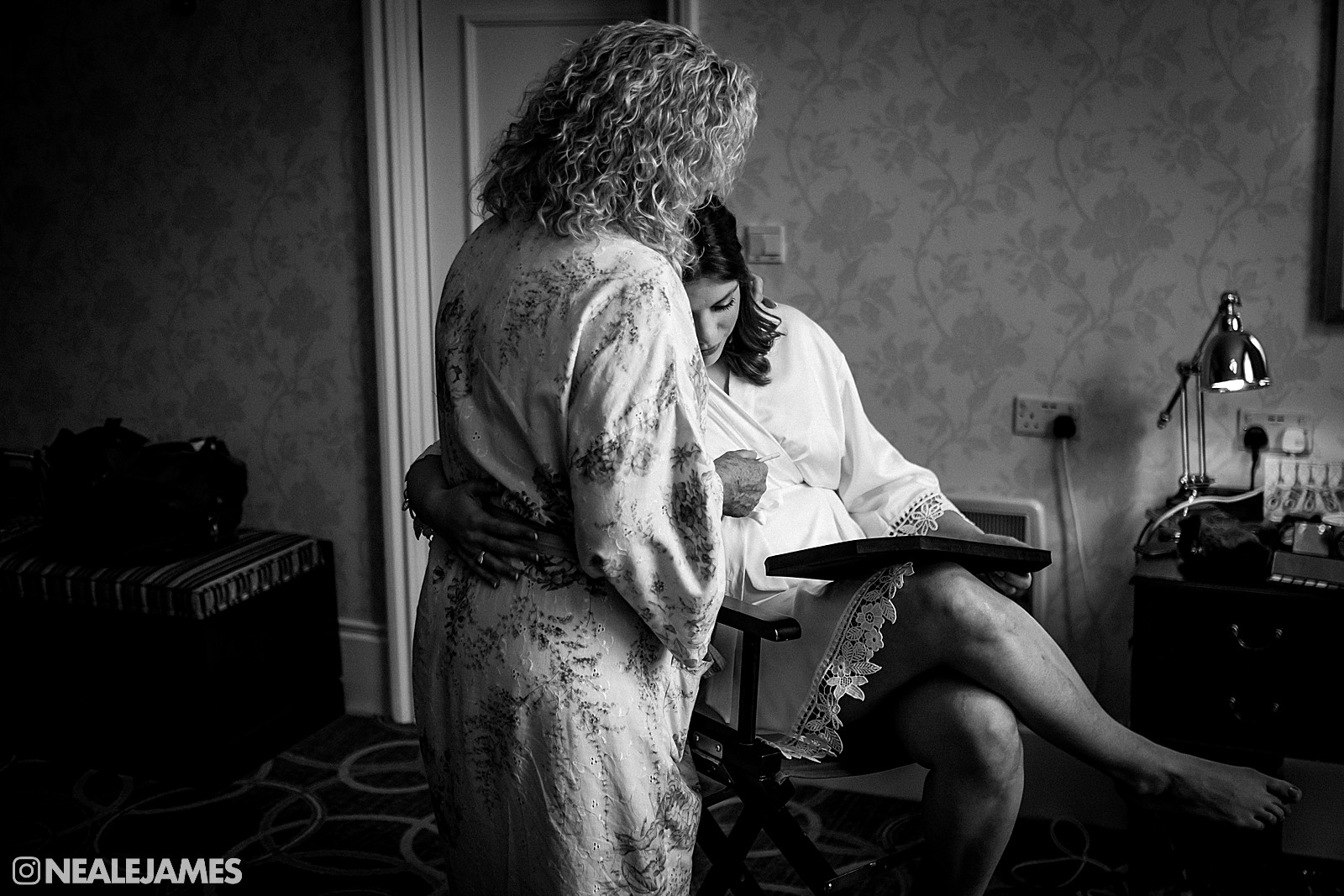 A black and white picture of a bride embracing her mother before a wedding