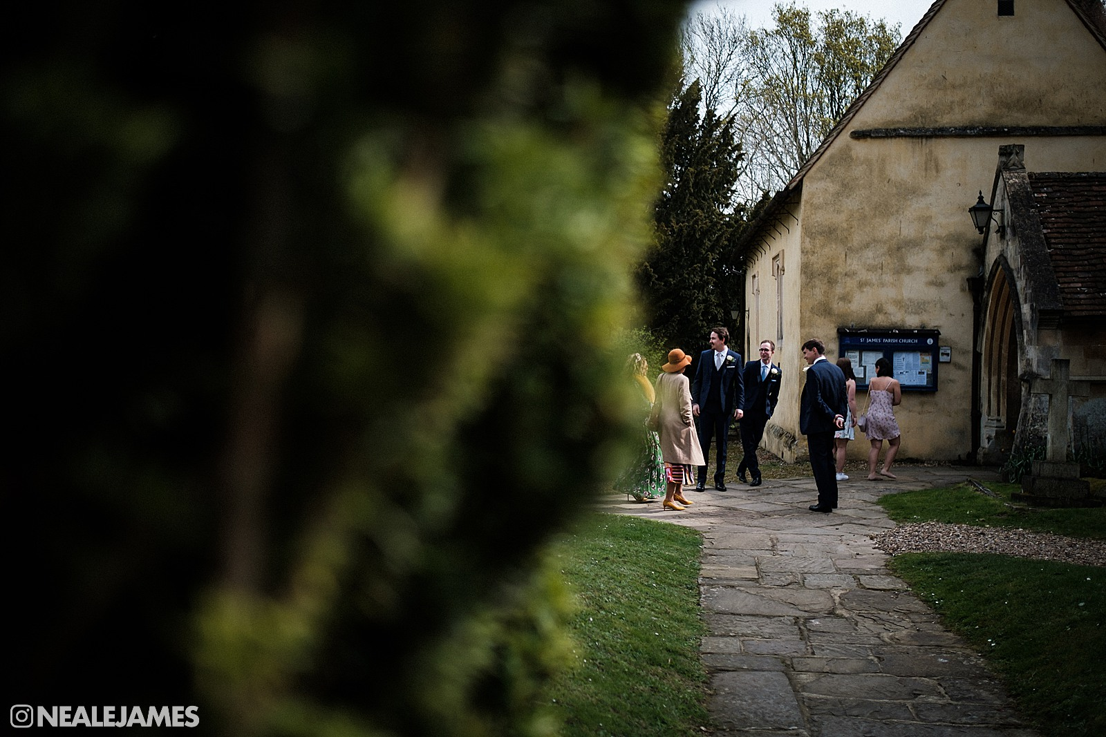 Colour picture of the groom at a wedding waiting outside a church in Hampshire