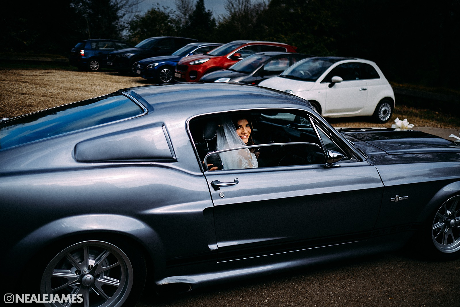 Colour photo of a bride arriving by Mustang car