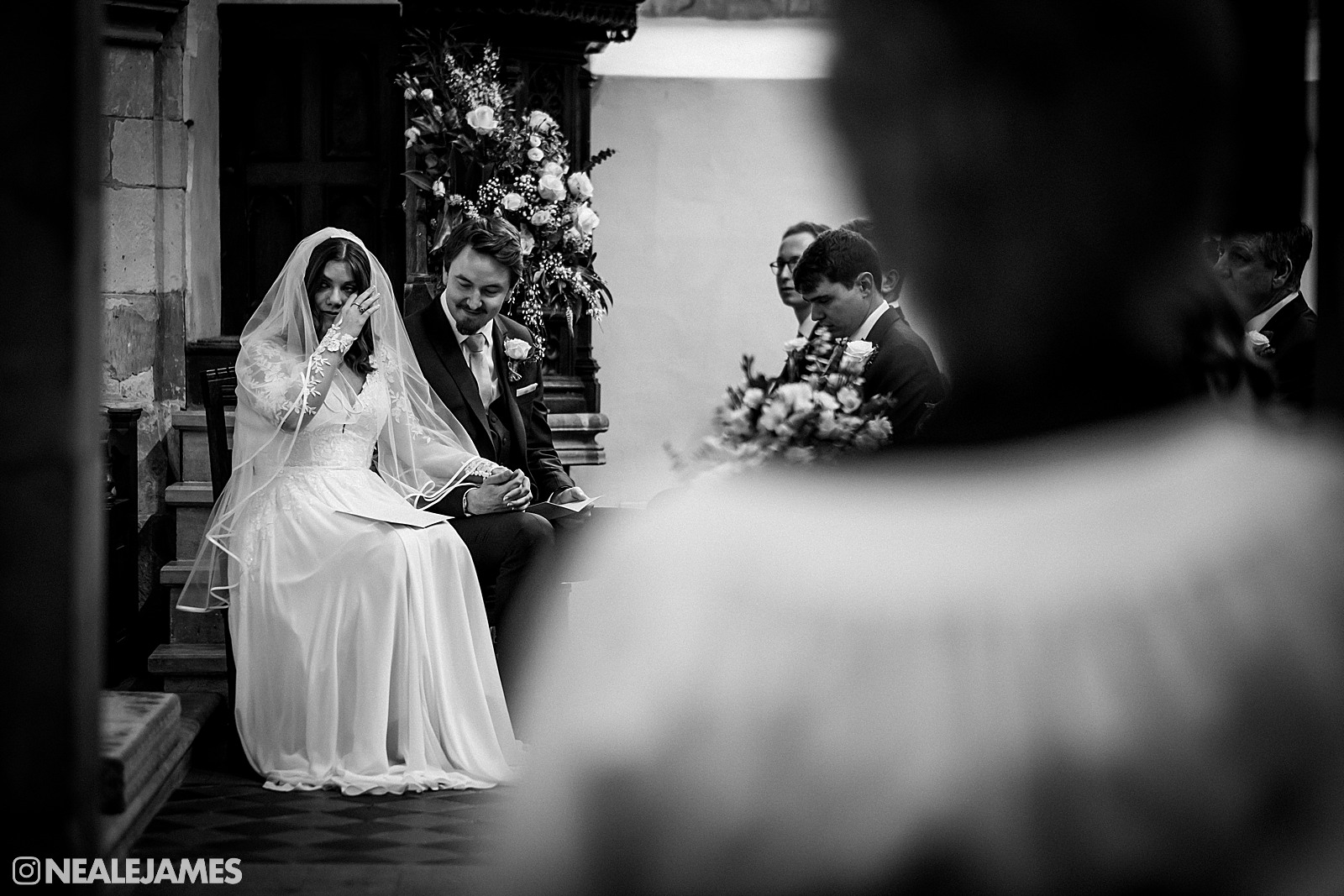 Black and white picture of a bride and groom being emotional during their church wedding