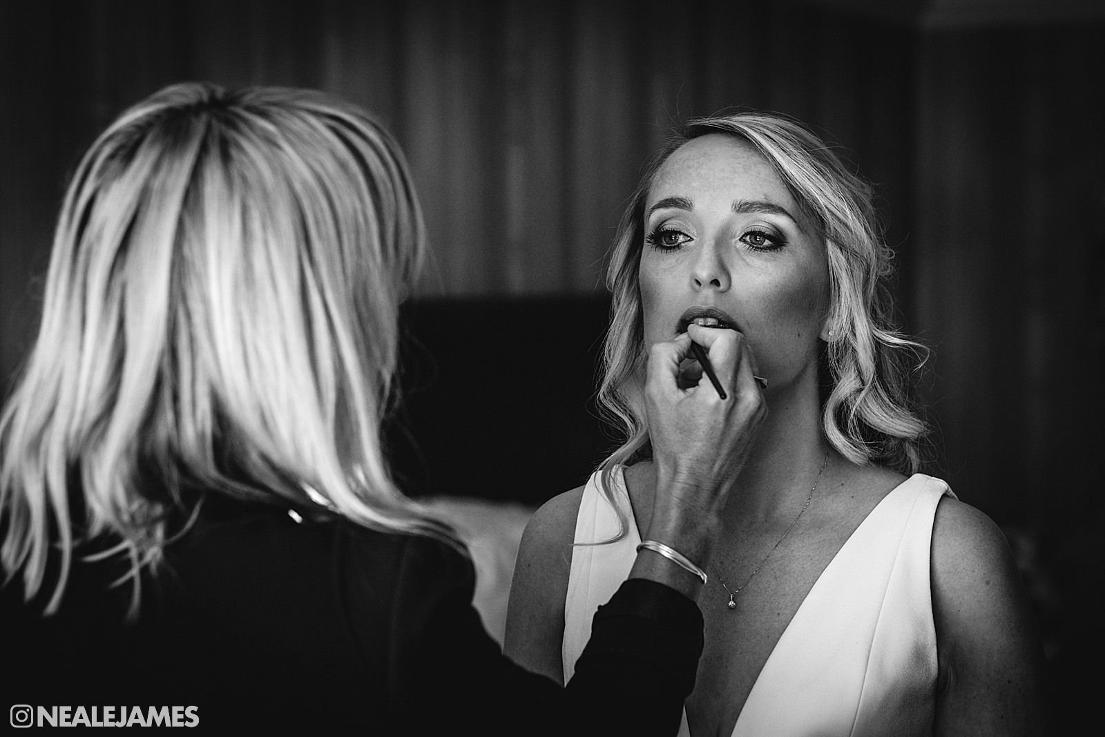 Black and white picture of a make up artist applying make up to a bride