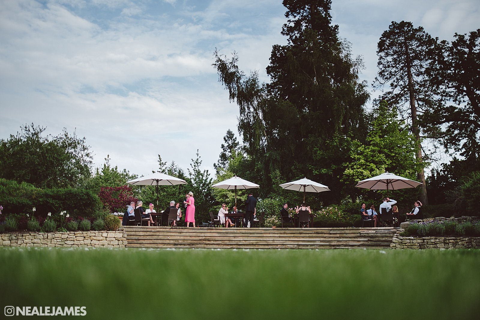 Colour photo of wedding guests relaxing in the grounds at The Vineyard